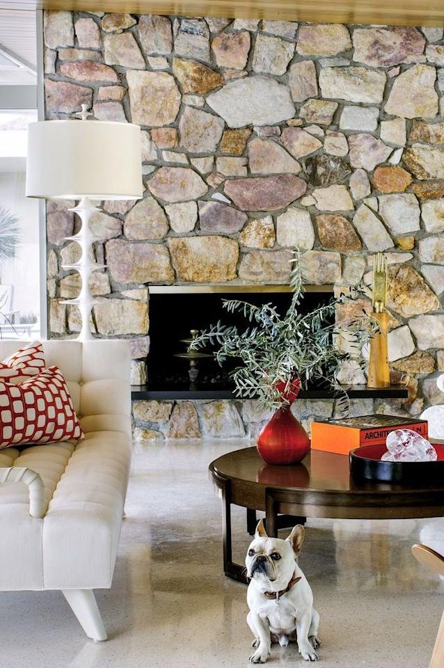 <p>An original stone fireplace is all this room needs to feel perfectly '70s, with a modern edge.</p>