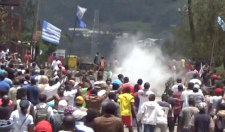 FILE PHOTO: A still image taken from a video shot on October 1, 2017, shows protesters waving Ambazonian flags as they move forward towards barricades and police amid tear gas in the English-speaking city of Bamenda, Cameroon. REUTERS/via Reuters TV/ File Photo
