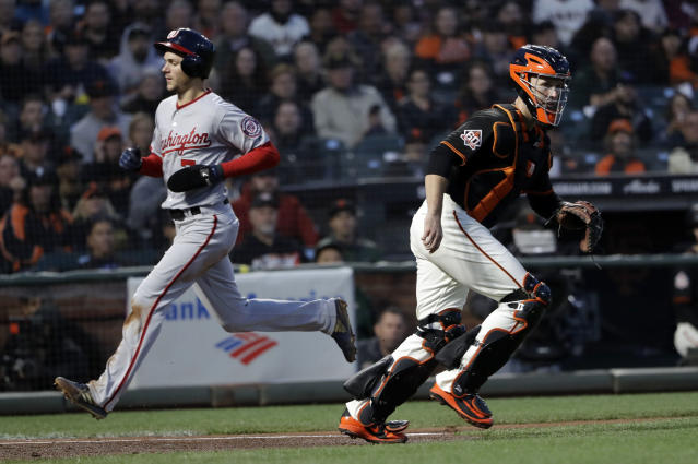Washington Nationals' Trea Turner scores past San Francisco Giants catcher Buster Posey on a sacrifice fly ball by Howie Kendrick during the third inning of a baseball game, Monday, April 23, 2018, in San Francisco. (AP Photo/Marcio Jose Sanchez)