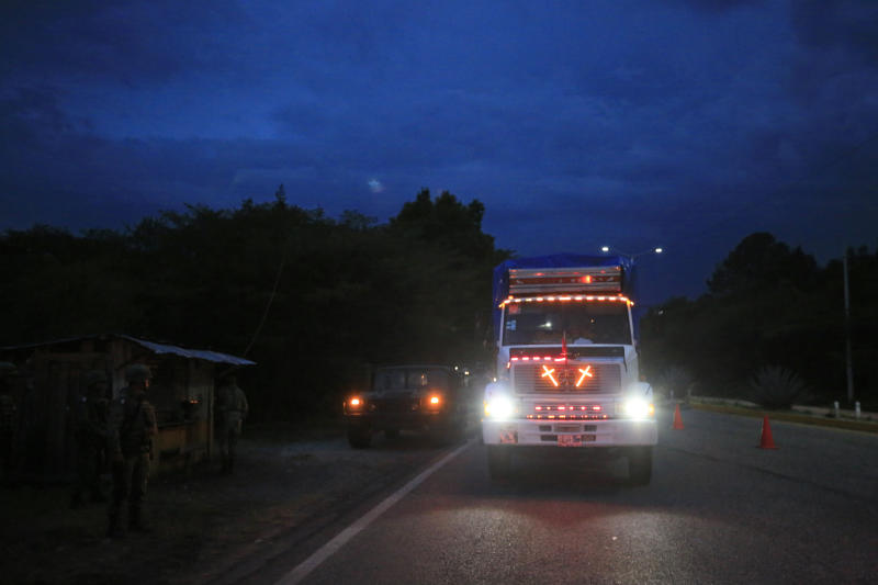 A truck decorated with crosses that light up when the driver brakes, slows down as it passes through a checkpoint, manned by soldiers from the National Guard along with immigration officers and federal police, in Comitan, Chiapas State, Mexico, Saturday, June 15, 2019. Under pressure from the U.S. to slow the flow of migrants north, Mexico plans to deploy thousands of National Guard troops by Tuesday to its southern border region.(AP Photo/Rebecca Blackwell)