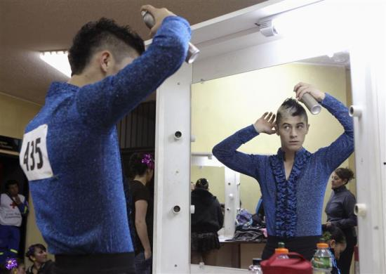 Colombian dancer Ivan Loaiza combs his hair before competing in the 3rd International Ecuador Salsa Congress at the House of Ecuadorian Culture in Quito, August 4, 2012.
