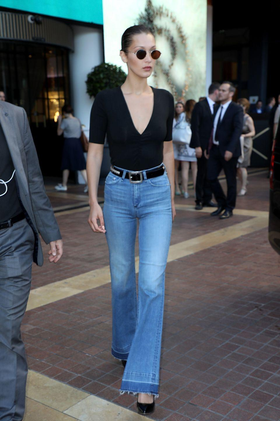 <p>In a deep V t-shirt, belted Rag & Bone flare jeans, black pumps and rounded sunglasses while out in Cannes. </p>