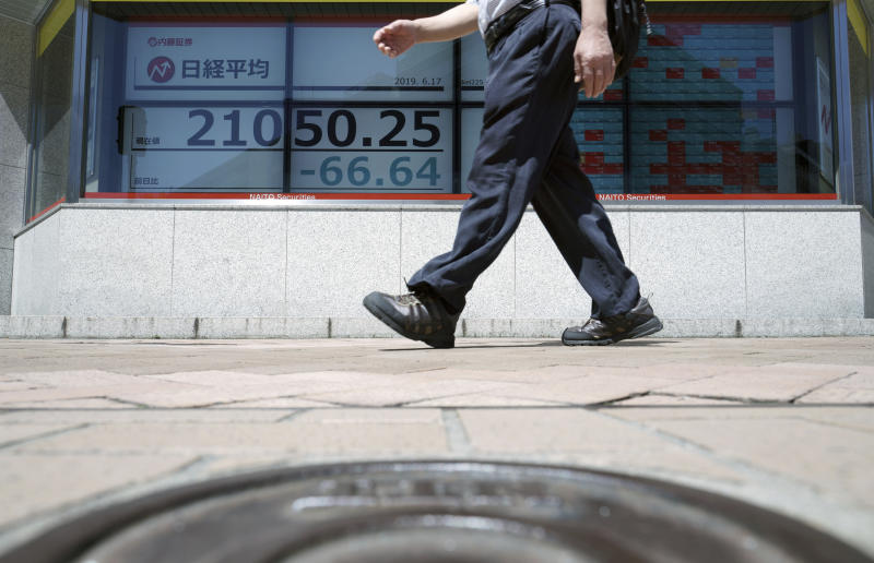 A man walks past an electronic stock board showing Japan's Nikkei 225 index at a securities firm in Tokyo Monday, June 17, 2019. Asian shares were mostly higher Monday amid a wait-and-see attitude about the direction of interest rates and the trade dispute between the U.S. and China. (AP Photo/Eugene Hoshiko)