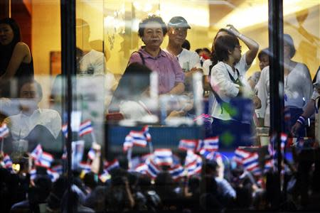 File photo of people looking on from inside a shopping mall as thousands protest against the amnesty bill in Bangkok's central business district