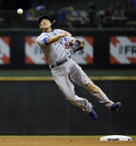 Chicago Cubs second baseman Darwin Barney throws to first on a ball hit by Milwaukee Brewers' Jean Segura during the sixth inning of a baseball game Wednesday, June 26, 2013, in Milwaukee. Segura beat the throw. (AP Photo/Morry Gash)