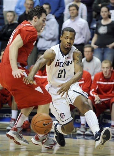 Connecticut's Omar Calhoun, right, drives past Stony Brook's Tommy Brenton during the first half of an NCAA college basketball game in Storrs, Conn., Sunday, Nov. 25, 2012. (AP Photo/Fred Beckham)