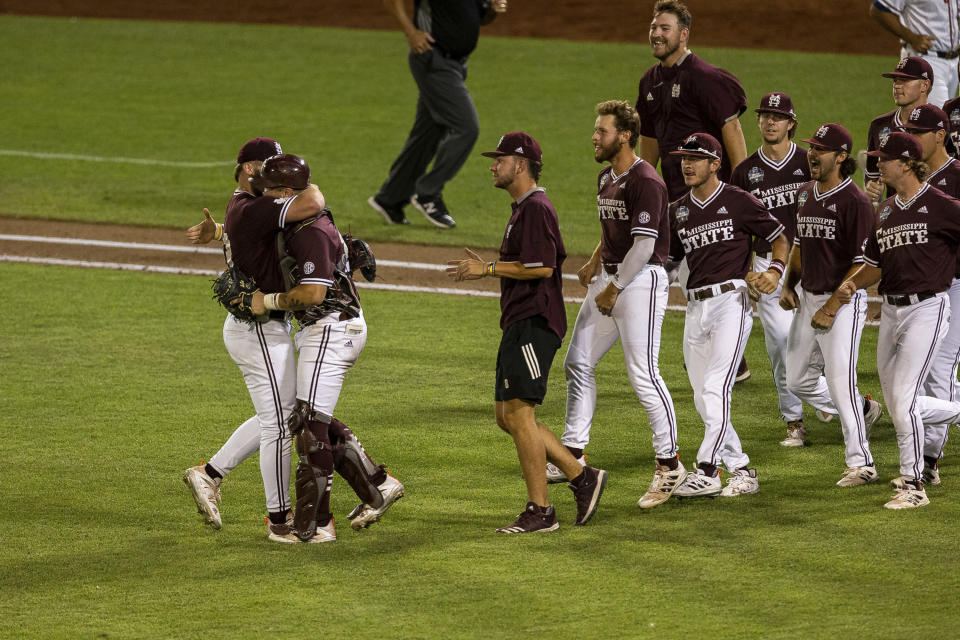 Mississippi State pitcher Landon Sims (23) receives a hug from catcher Logan Tanner (19) after their win over Virginia during a baseball game in the College World Series Tuesday, June 22, 2021, at TD Ameritrade Park in Omaha, Neb. (AP Photo/John Peterson)
