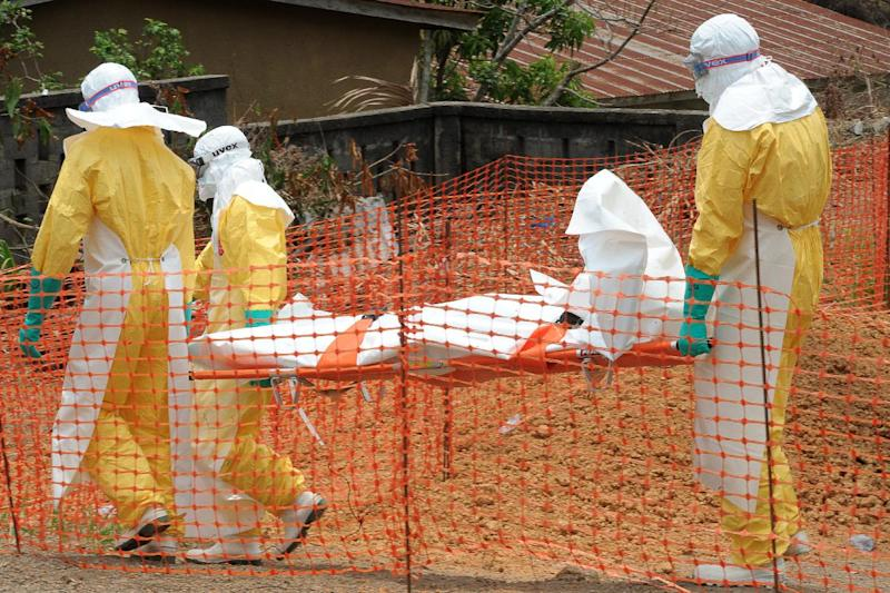 Staff of the 'Doctors without Borders' ('Medecin sans frontieres') medical aid organisation carry the body of a person killed by the Ebola virus, at a center for victims of the viral haemorrhagic fever in Guekedou, on April 1, 2014