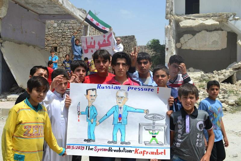 """In this citizen journalism image provided by Edlib News Network, ENN, which has been authenticated based on its contents and other AP reporting, anti-Syrian regime protesters hold a poster depicting Syrian President Bashar Assad, left, and Russian Foreign Minister Sergei Lavrov, right,  during a demonstration, at Kafr Nabil town, in Idlib province, northern Syria, Friday May 10, 2013. Arabic banner on the background reads, """"Kafr Nabil."""" (AP Photo/Edlib News Network ENN)"""
