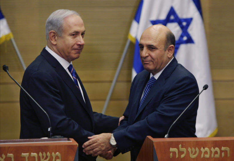 "Israel's Prime Minister Benjamin Netanyahu, left, and Kadima party leader Shaul Mofaz shake hands before holding a joint press conference announcing the new coalition government in Jerusalem, Tuesday, May 8, 2012. Netanyahu said Tuesday his new coalition government will promote a ""responsible"" peace process with the Palestinians. (AP Photo/Sebastian Scheiner)"