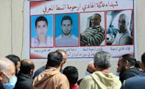 Libyans gather by a wall poster depicting victims from one family during a funeral procession for 12 bodies that were identified from mass graves found in Tarhuna town