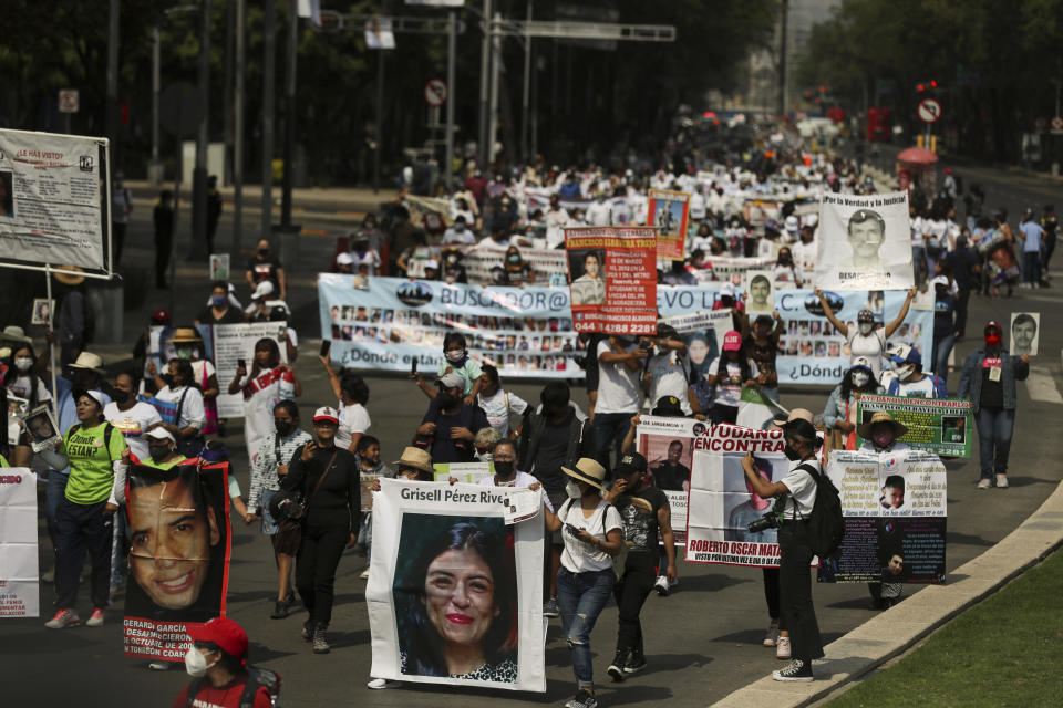 People carry photographs during a march in remembrance of those who have disappeared, on Mother's Day in Mexico City, Monday, May 10, 2021. (AP Photo/Fernando Llano)