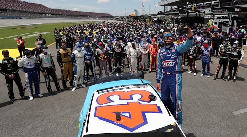 TALLADEGA, ALABAMA - JUNE 22: Bubba Wallace, driver of the #43 Victory Junction Chevrolet, takes a selfie with NASCAR drivers that pushed him to the front of the grid as a sign of solidarity with the driver prior to the NASCAR Cup Series GEICO 500 at Talladega Superspeedway on June 22, 2020 in Talladega, Alabama. A noose was found in the garage stall of NASCAR driver Bubba Wallace at Talladega Superspeedway a week after the organization banned the Confederate flag at its facilities. (Photo by Chris Graythen/Getty Images)