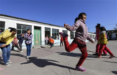 Students play a rope-skipping game during a break at Pengying School on the outskirts of Beijing