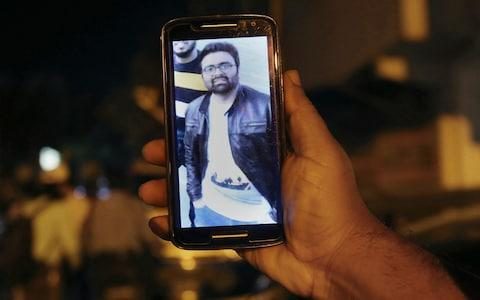 A relative shows the picture of Syed Areeb Ahmed, a Pakistani citizen who was killed the Christchurch mosque shooting, on his cell phone outside his home in Karachi - Credit: AP