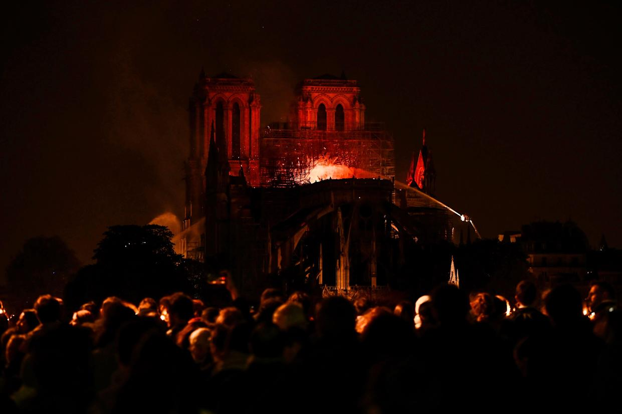 Bystanders look on as flames and smoke billow from the roof. (Photo: Philippe Lopez/AFP/Getty Images)