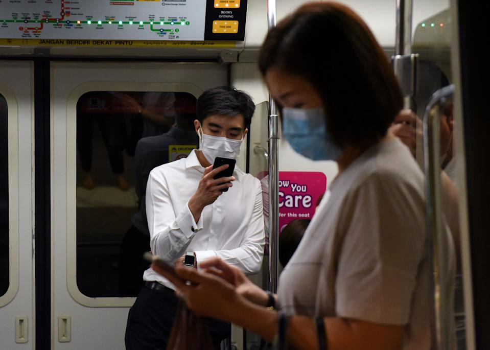 Commuters wearing face masks as a preventive measure against COVID-19 look at their mobile phones on the MRT on 18 March, 2020. (PHOTO: AFP via Getty Images)
