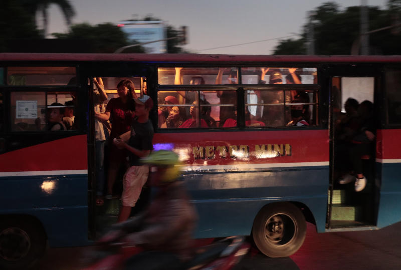 People ride on a public bus during a power outage in Jakarta, Indonesia, Sunday, Aug. 4, 2019. Indonesia's sprawling capital and other parts of Java island have been hit by a massive power outage affecting millions of people. (AP Photo/Dita Alangkara)