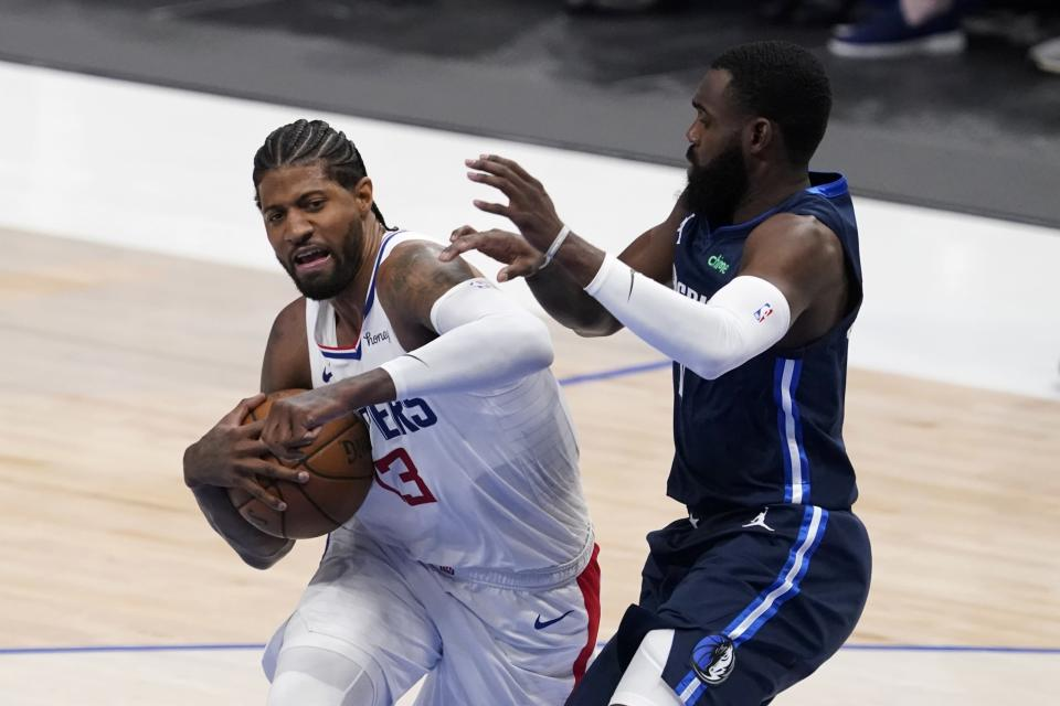 Los Angeles Clippers guard Paul George (13) fights to the basket against Dallas Mavericks' Tim Hardaway Jr, right, in the first half in Game 3 of an NBA basketball first-round playoff series in Dallas, Friday, May 28, 2021. (AP Photo/Tony Gutierrez)