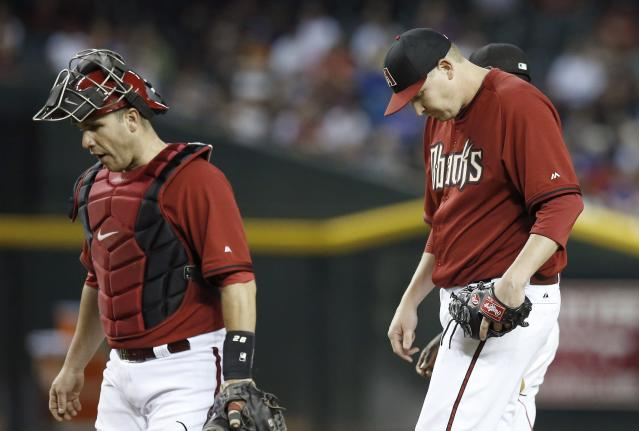 Arizona Diamondbacks' Trevor Cahill, right, looks down after getting a visit from catcher Miguel Montero after Cahill gave up a run to the Chicago Cubs in the fourth inning of a spring training baseball game, Friday, March 28, 2014, in Phoenix. (AP Photo/Ross D. Franklin)