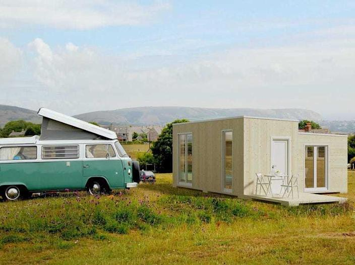 A portable off-grid Brette Haus Tiny Home rests in a field next to a VW van.