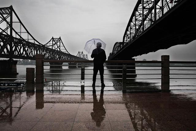 "<p>A Chinese man stands in the rain between ""Friendship Bridge"", left, and ""Broken Bridge"", right, as he looks across the Yalu river from the border city of Dandong, Liaoning province, northern China towards the city of Sinuiju, North Korea on May 23, 2017 in Dandong, China. (Photo: Kevin Frayer/Getty Images) </p>"