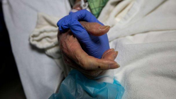 PHOTO: Registered Nurse Ana Ramos holds the hand of a 91-year-old COVID-19 patient inside the ICU at Providence St. Jude Medical Center on Dec. 25, 2020, in Fullerton, Calif. (Francine Orr/Los Angeles Times via Getty Images)