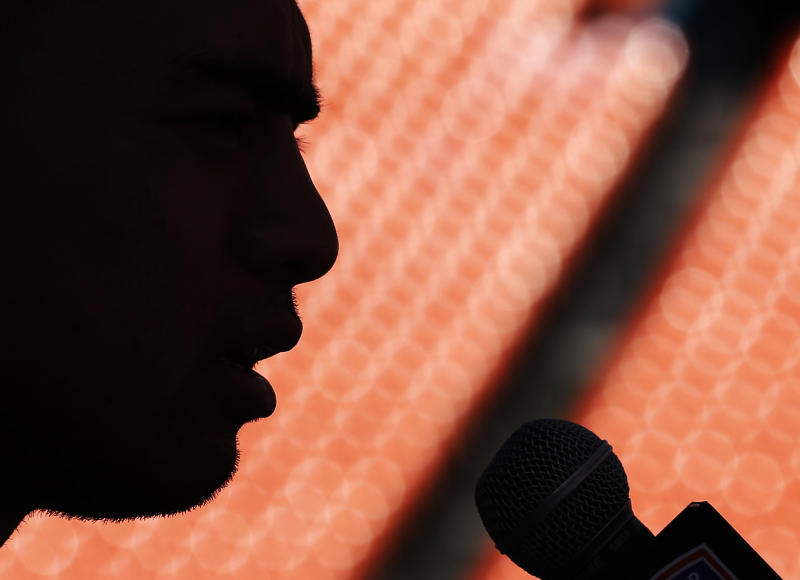 FILE - In this Jan. 5, 2013, file photo, Notre Dame linebacker Manti Te'o answers a question during media day for the BCS national championship NCAA college football game in Miami. The Heisman Trophy runner-up had told heartbreaking stories about a dead girlfriend who didn't exist. Then it became unreal: The All-American linebacker said he had been duped, and theirs was a relationship that existed only in phone calls and Internet chats. People speculated he must be a straight-laced Mormon, naive and unfamiliar with modern-day dating hazards. Or he must be part of an elaborate hoax designed to bolster his image. Because no big-time college football player, beloved on campus and adored by millions, could have a girlfriend he's never ... actually ... met. (AP Photo/David J. Phillip, File)