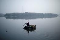A man rows a makeshift boat across Yamuna river on a smoggy morning in New Delhi