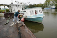 Perry Menesses tosses a rope to Will Guillot as they wanted to secure their boat with more rope after hearing that Hurricane Zeta has increased in strength, in Violet, La., Wednesday, Oct. 28, 2020. Hurricane Zeta is expected to make landfall this afternoon as a category 2 storm. (AP Photo/Gerald Herbert)