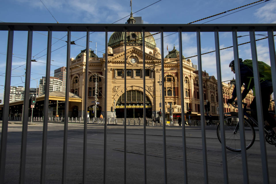 A cyclists passes an empty Flinders Street Station during lockdown due to the continuing spread of the coronavirus in Melbourne, Thursday, Aug. 6, 2020. Victoria state, Australia's coronavirus hot spot, announced on Monday that businesses will be closed and scaled down in a bid to curb the spread of the virus. (AP Photo/Andy Brownbill)