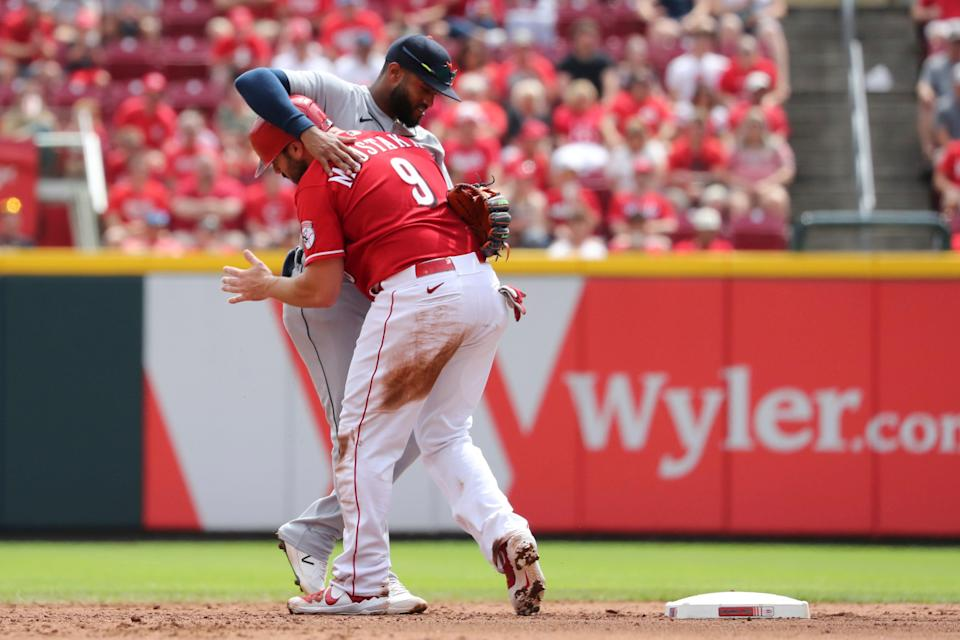 Cincinnati Reds baserunner Mike Moustakas (9) becomes entangled with Detroit Tigers shortstop Willi Castro, rear, after being forced out at second base on a fielder's choice off the bat of Reds' Kyle Farmer during the fifth inning of a baseball game, Sunday, Sept. 5, 2021, in Cincinnati.