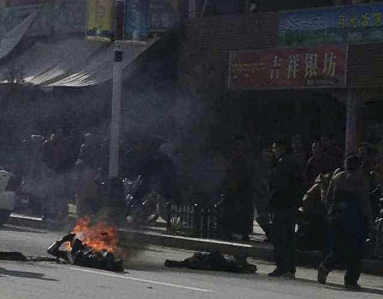In this photo taken Tuesday Oct 23, 2012 and released by Washington-based International Campaign for Tibet, Dorje Rinchen, a farmer in his late 50s, is seen on the ground burning after setting himself on fire on the main street in Xiahe in northwestern China's Gansu province. This was the second self-immolation death in two days near the Labrang monastery in Xiahe. The monastery is one of the most important outside of Tibet and was the site of numerous protests by monks following deadly ethnic riots in Tibet in 2008 that were the most sustained Tibetan uprising against Chinese rule in decades.(AP Photo/International Campaign for Tibet) EDITORIAL USE ONLY, NO SALES