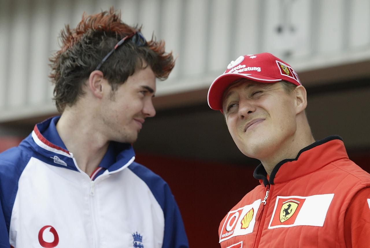 SILVERSTONE, ENGLAND - JULY 18:  England cricketer James Anderson chats to Michael Schumacher of Germany and Ferrari prior to the Formula One British Grand Prix at Silverstone on July 18, 2003 in Northamptonshire, England. (Photo by Clive Mason/Getty Images)