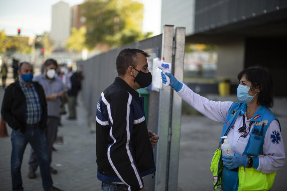A Madrid Emergency Service (SUMMA) health worker checks the temperature of a man prior to a rapid antigen test for COVID-19 in the southern neighbourhood of Vallecas in Madrid, Spain, Wednesday, Oct. 7, 2020. About 5.2 million people in Spain, including nearly 4.8 million residents in or around Madrid, are under restrictions on movement due to the second wave of the coronavirus pandemic. (AP Photo/Manu Fernandez)