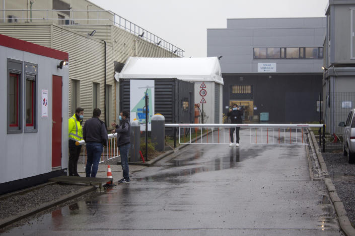 A security guard talks to people at the entrance of Novasep factory in Seneffe, Belgium, Thursday, Jan. 28, 2021. Belgian health authorities said Thursday they have inspected a pharmaceutical factory located in Belgium to find out whether the expected delays in the deliveries of AstraZeneca's coronavirus vaccines are due to production issues. The Novasep factory in the town of Seneffe is part of the European production chain for AstraZeneca's coronavirus vaccine. (AP Photo/Mark Carlson)