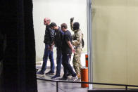 A gunman with a weapon in hand, escorts three police officers, who surrendered themselves as hostages, out of the bank building in the town of Zugdidi in western Georgia, Wednesday, Oct. 21, 2020. Authorities in the ex-Soviet republic of Georgia say an armed assailant has taken hostages at a bank. Local media reported that up to 19 hostages could be inside the bank. The Georgian Interior Ministry didn't immediately comment on how many people were taken hostage Wednesday in the western town of Zugdidi or what demands their captor had made. (AP Photo/Zurab Tsertsvadze)