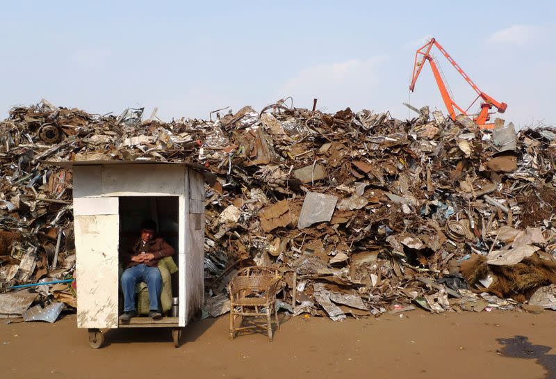 FILE PHOTO: A worker naps in front of scrap metal dump site at a import dock in Taizhou
