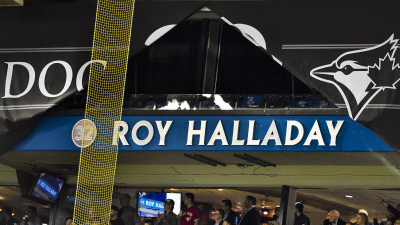 TORONTO, ON - MARCH 29: Roy Halliday's name is revealed, newly appointed on a stadium fascia in a ceremony honoring the late Jay's pitcher before the MLB season game between the New York Yankees and the Toronto Blue Jays at Rogers Centre in Toronto, ON., Canada March 29, 2018. The Blue Jays also retired his No. 32 on opening day. Jays players will wear a no. 32 patch on their jerseys throughout the season in tribute to Halladay. Halladay, nicknamed 'Doc' who spent 12 seasons as a pitcher with the Jays, died in November 2017 when his personal plane crashed into the Gulf of Mexico near Tampa. He was 40 years old. Halladay joins Robero Alomar (no. 12) as the only 2 players in Jays history to have their jersey numbers retired. (Photo by Jeff Chevrier/Icon Sportswire via Getty Images)