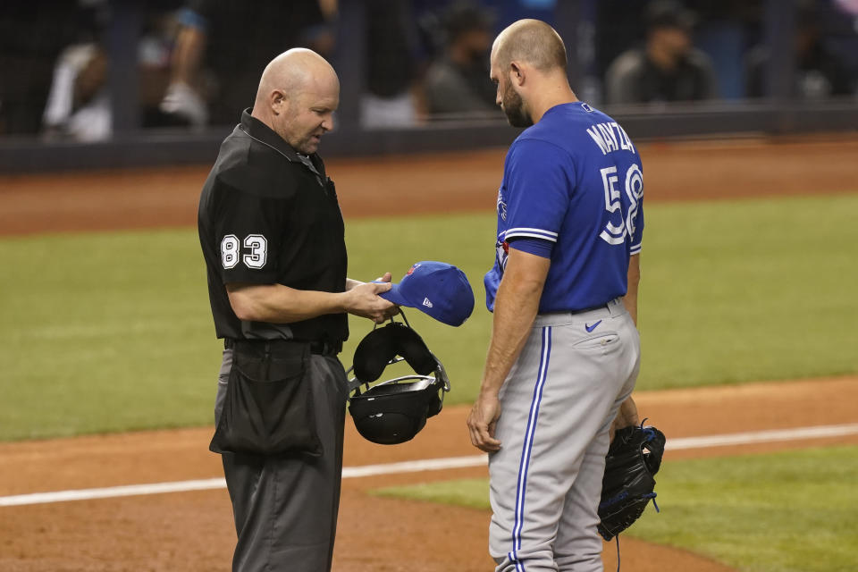 MLB umpire Mike Estabrook (83) inspect the hat of Toronto Blue Jays relief pitcher Tim Mayza (58) during the eighth inning of a baseball game against the Miami Marlins, Wednesday, June 23, 2021, in Miami. (AP Photo/Marta Lavandier)