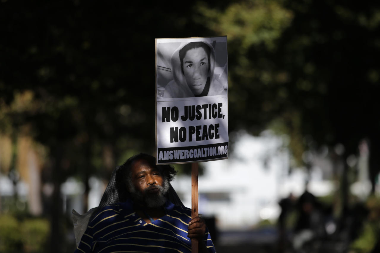 John Simpson, 56, carries a sign showing an image of Trayvon Martin during a demonstration in reaction to the acquittal of neighborhood watch volunteer George Zimmerman on Monday, July 15, 2013, in Los Angeles. Anger over the acquittal of the U.S. neighborhood watch volunteer who shot dead an unarmed black teenager continued Monday, with civil rights leaders saying mostly peaceful protests will continue this weekend with vigils in dozens of cities. (AP Photo/Jae C. Hong)