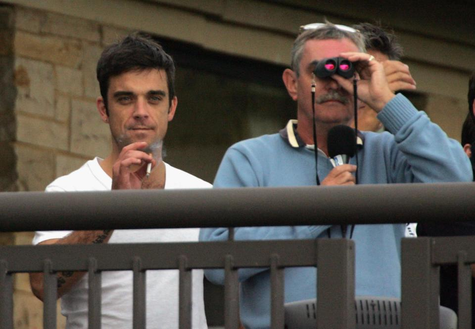 NEWPORT, WALES - AUGUST 29: Robbie Williams (L) watches the match on the final day of The All-Star Cup Celebrity Golf tournament at the Celtic Manor Resort on August 29, 2005 Newport, Wales. The cup, brainchild of Anthony McPartlin and Declan Donnelly, sees 2 teams of 10 celebrities from Europe and the US taking part over the Roman Road course, venue of the 2010 Ryder Cup, with Colin Montgomerie and Mark O?Meara as the non-playing captains of the European and US teams respectively.  The cup will be presented by Kirsty Gallacher and Jamie Theakston. (Photo by Matt Cardy/Getty Images)