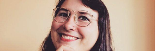 Photo of the writer, a younger white woman wearing glasses and smiling. Her hand is on her chin.