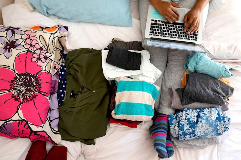 A woman works on a laptop to sell her clothes.