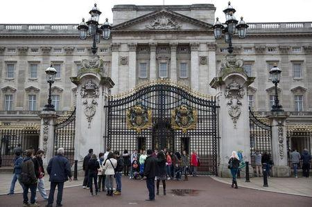 Tourists pose for photographs in front of Buckingham Palace in central London