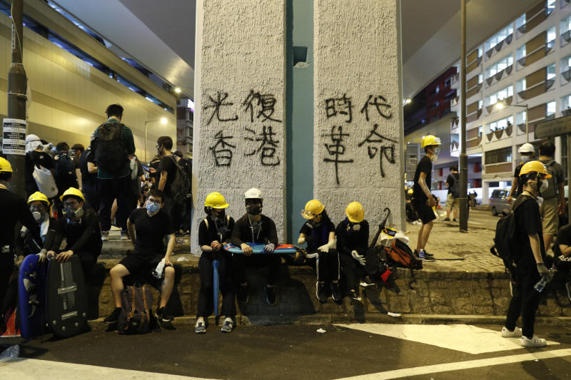 """Protesters rest near graffiti which reads """"Recovery of Hong Kong, An Era Revolution"""" in Hong Kong on Sunday, July 21, 2019. Protesters in Hong Kong pressed on Sunday past the designated end point for a march in which tens of thousands repeated demands for direct elections in the Chinese territory and an independent investigation into police tactics used in previous demonstrations. (AP Photo/Vincent Yu)"""