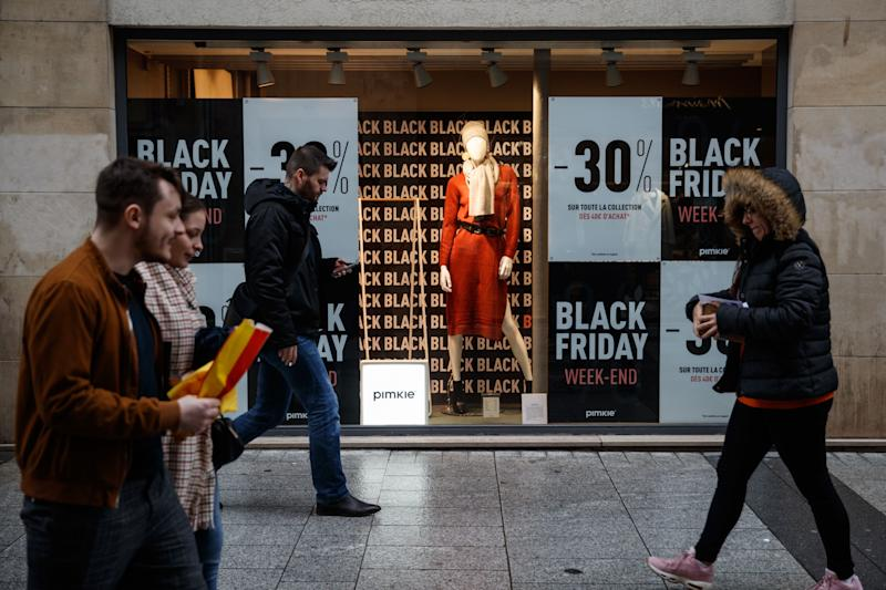 Pedestrians walk past a shop announcing Black Friday sales in Caen, northwestern France, on November 27, 2019. - Black Friday is a sales offer originating from the US where retailers slash prices on the day after the Thanksgiving holiday. (Photo by Sameer Al-DOUMY / AFP) (Photo by SAMEER AL-DOUMY/AFP via Getty Images)