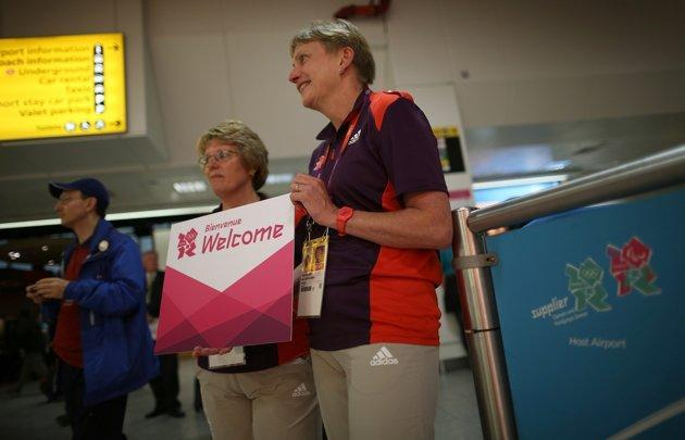 LONDON, ENGLAND - JULY 16: Olympic volunteers wait to greet arriving teams at Heathrow Airport on July 16, 2012 in London, England. Athletes, coaches and Olympic officials are beginning to arrive in London ahead of the Olympics.