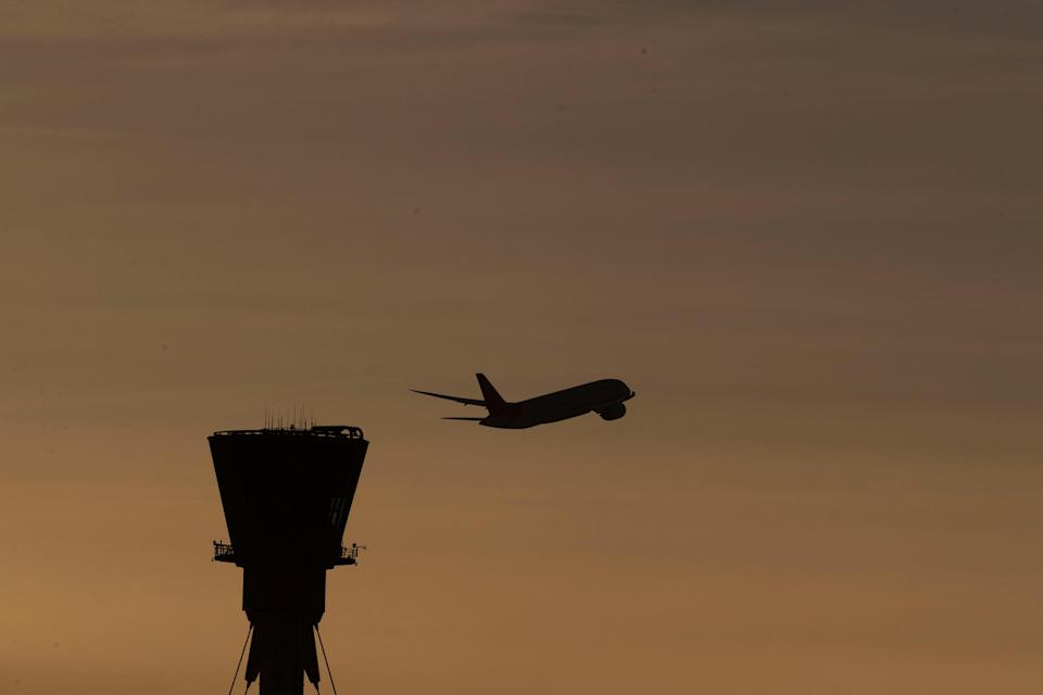 A plane takes off past the control tower at Heathrow Airport (Steve Parsons/PA) (PA Archive)