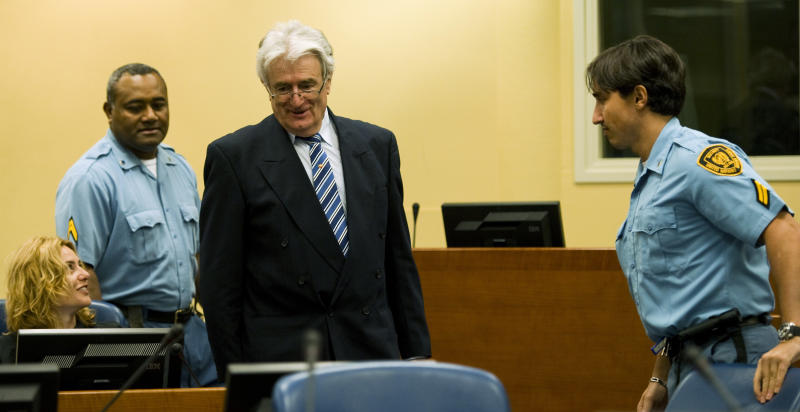 Suspected war criminal and the former leader of Serbs in Bosnia, Radovan Karadzic, center, smiles when taking his seat on the defense bench in the court room to start his defense at the U.N. war crimes tribunal in the Hague in The Hague, Netherlands, Tuesday Oct. 16, 2012. (AP Photo/Robin van Lonkhuijsen, pool)